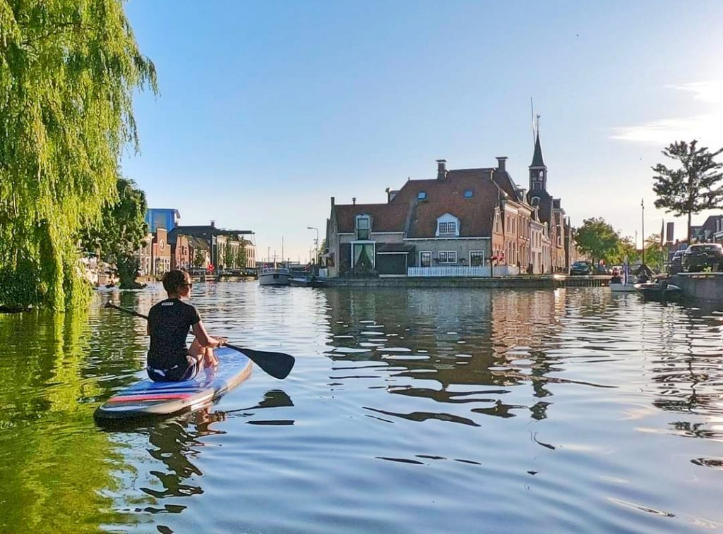 Boy on a SUP in a city